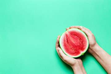 Half of Sweet Mini Watermelon in Female Hands with Green Copy Space