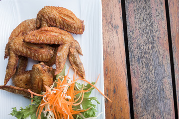 Chichen wing fried with salad in white dish on wooden table with copyspace ,flat lay