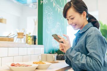 スマートフォンで料理の写真を撮る女性
