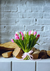 Bouquet of tulips with pink ribbon on the gray brick wall background