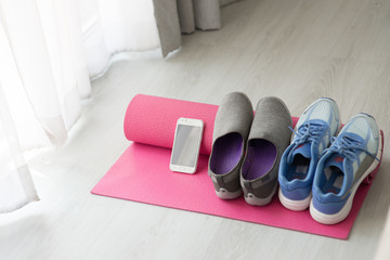 Blue, gray and purple Sport shoes, yoga mat, smartphone on gray background.