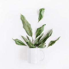 Blank template of white mug and green leaves bouquet on white background. Flat lay, top view.