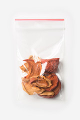 Plastic transparent zipper bag with home dried apples isolated on white, Vacuum package mockup with red clip. Concept.