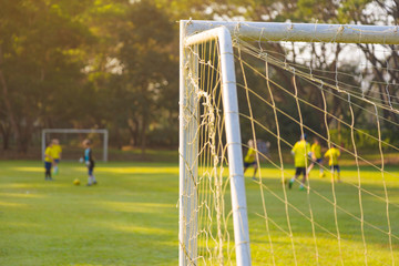 corner of a soccer or football goal post with warm morning light and blurred players in background