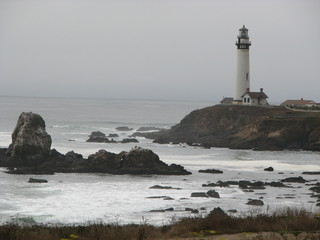 lighthouse and large rocks in ocean
