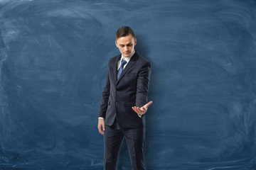 Businessman on blue chalkboard background holding one hand out and looking at it.