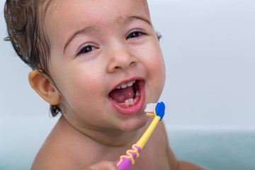 cute little girl bathes in a bath and brushing his teeth, the concept of hygiene and cleanliness