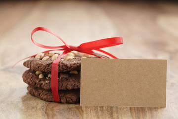 stack of homemade chocolate cookies with hazelnuts tied with ribbon on wood table and paper card
