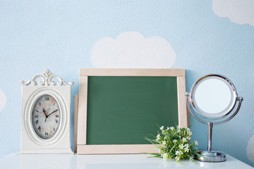 Blank drawing board, table clock, mirror,flowers