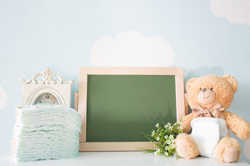 Diapers and blank chalkboard. Teddy bear dressed in diaper. top view. frame with a copy space