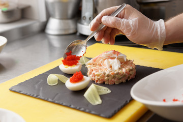 Chef is decorating crab salad in commercial kitchen