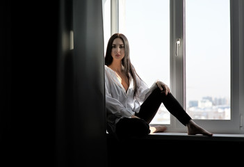 sexy brunette sits on the windowsill in a white chaff. Black background, bright fluorescent light, high floor, silhouette, black and white