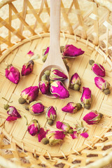dried tea rose in a wooden spoon. selective focus.