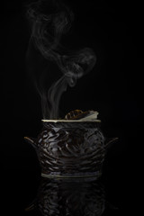 Cooking in a clay pot on a black background.