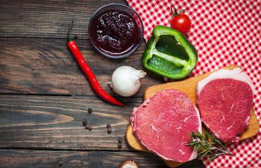 Fresh raw beef steak and pepper on wood