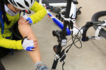 female cyclist getting injured while falling from mountain bike on forest trail