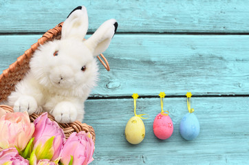 rabbits in the basket with Easter eggs and flower