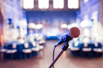 Microphone over the Abstract blurred photo of conference hall or wedding banquet background