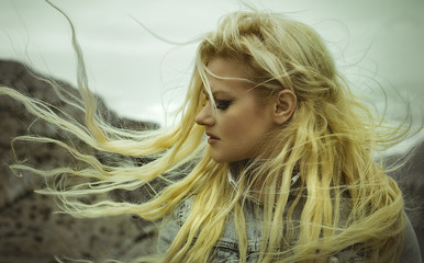 Beautiful, blond woman with long hair moved by the wind on a paradise island