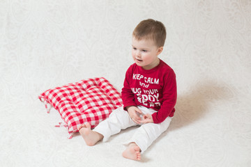 a child with a keep calm pullover sitting on a floor in a white room