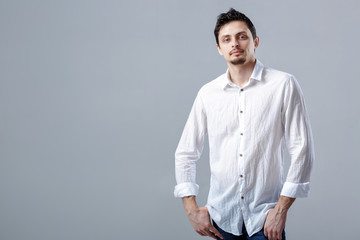 portrait of handsome young man with dark hair in white shirt on