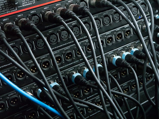XLR cables plugged into different inputs and outputs at a recording studio
