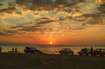 Beautiful blazing sunset landscape at Caspian sea and orange sky above it with awesome sun golden reflection on calm waves as a background. Amazing sunset view on the beach. Azerbaijan Absheron, Baku