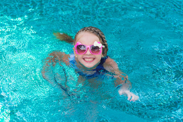 cheerful girl child resting in pool wearing sunglasses