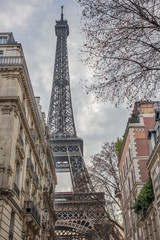 The Eiffel tower, towering over the surrounding houses on a cloudy winter day