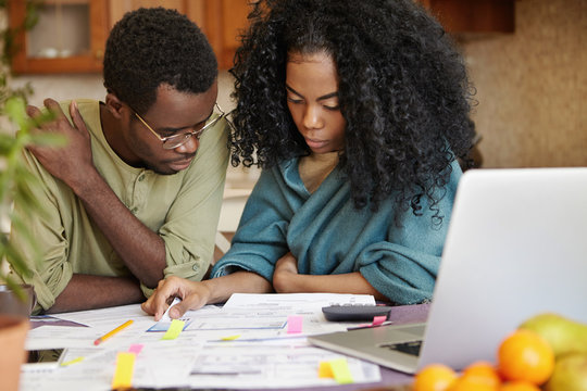 African couple reviewing their finances, analyzing family budget, thinking how to cut off expenses to be able to save money and buy new car, sitting at kitchen table with documents and laptop
