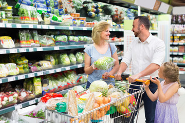 Family picking greens in food store.