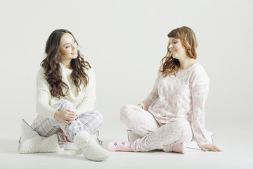Girls in pajamas sitting talking on a white background isolated