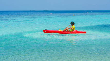Young caucasian man kayaking in sea at Maldives - Boost up color Processing.