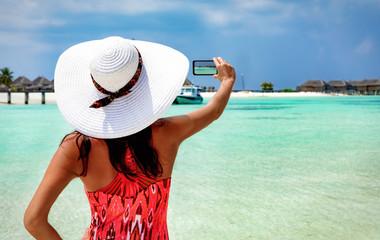 Touristin auf den Malediven fotografiert den Strand