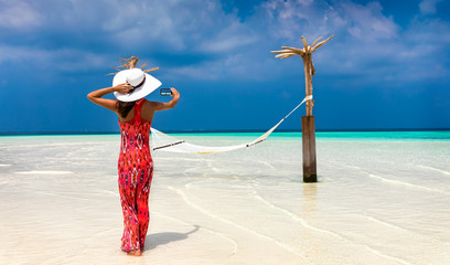 Frau im roten Kleid fotografiert einen Strand mit Hängematte auf den Malediven