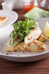 Healthy Breakfast, pancakes with salmon, cheese mousse, herbs, on a wooden table. Selective focus