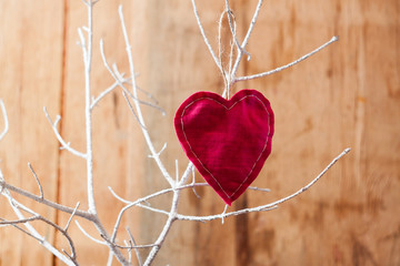 Heart from cloth on white branch