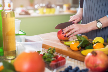 Hands cutting an apple on chopping board. Young woman preparing a fruit salad in her kitchen