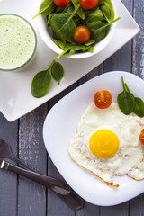 Food fried egg spinach salad wood background