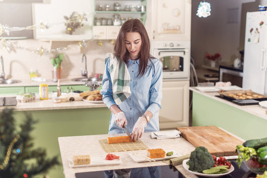 Female cook working in gloves making Japanese sushi rolls slicing them on bamboo mat standing in kitchen