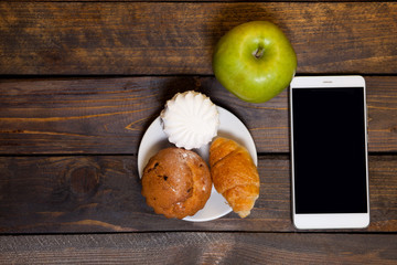 Coffee in white cup and cell phone with croissants, muffins, marshmallows, and green apple