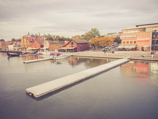 Vintage style: TONSBERG, NORWAY - October 7, 2013 Tonsberg waterfront, Brygge, with restaurant, Norway