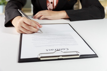 Hands of business woman signing the contract document with pen on desk - business concept