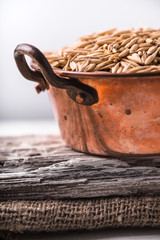 Oats in a copper bowl on a wooden stand on the napkin