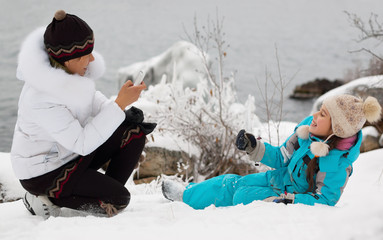 Mother and young daughter have fun in the winter at the lake