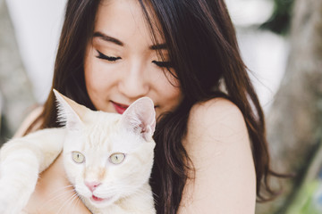 young chinese woman loving her cat