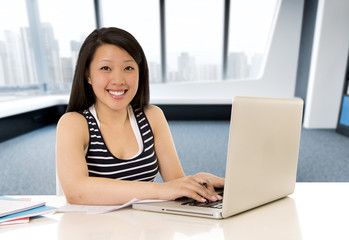 chinese asian woman working and studying on her laptop at modern office computer desk