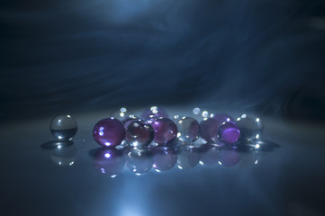 Marble crystal clear ball, rainbow multicolored glitter sparkles background. Selective focus. Multicolored