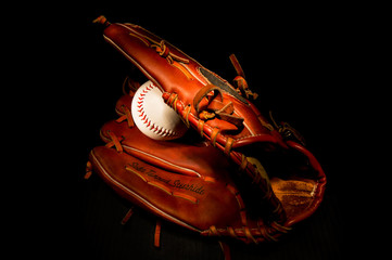 Baseball and glove on black background