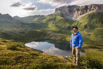 Traveler around the mountain lakes and rocky peaks at sunset